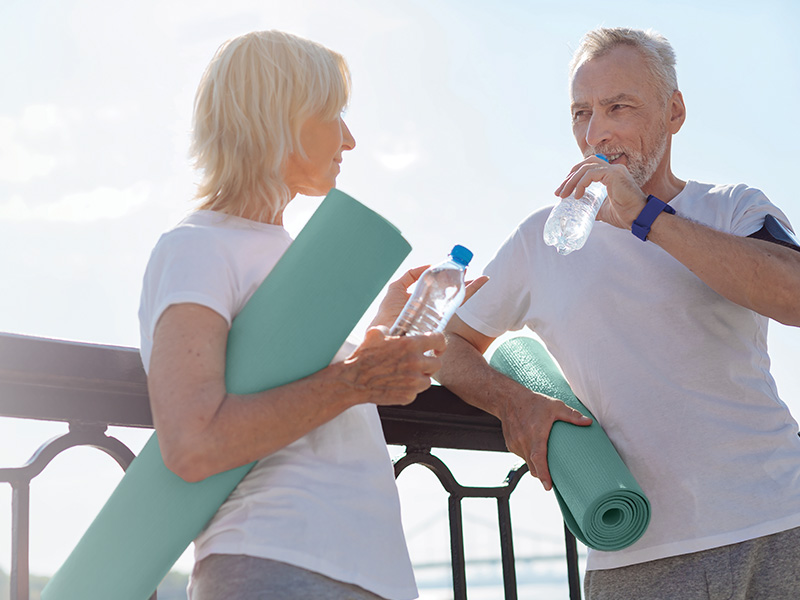 Healthy agers holding yoga mats