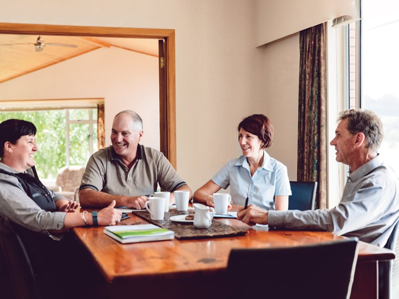 Fonterra farmers and employees talking at a table drinking tea