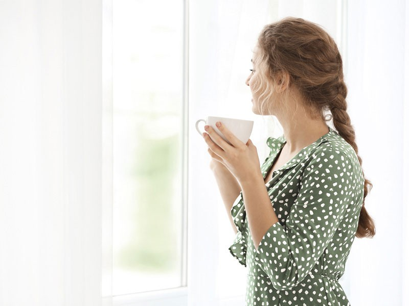 Woman in green dress drinking a cup of tea by window