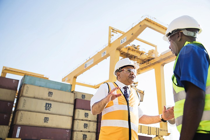 Two Men Speak Near Heavy Machinery and Containers, Talent - Mohamed El Garawany - Employee