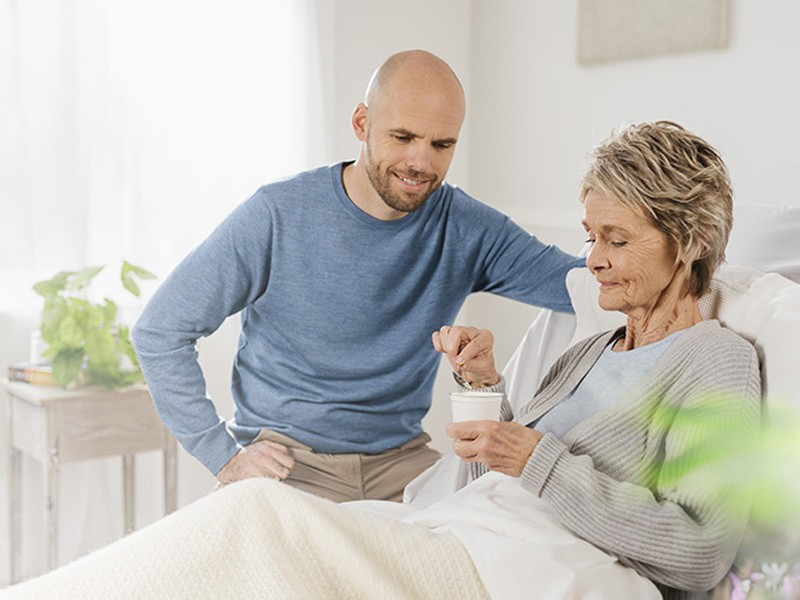 Elderly woman in bed with son eating from a pot