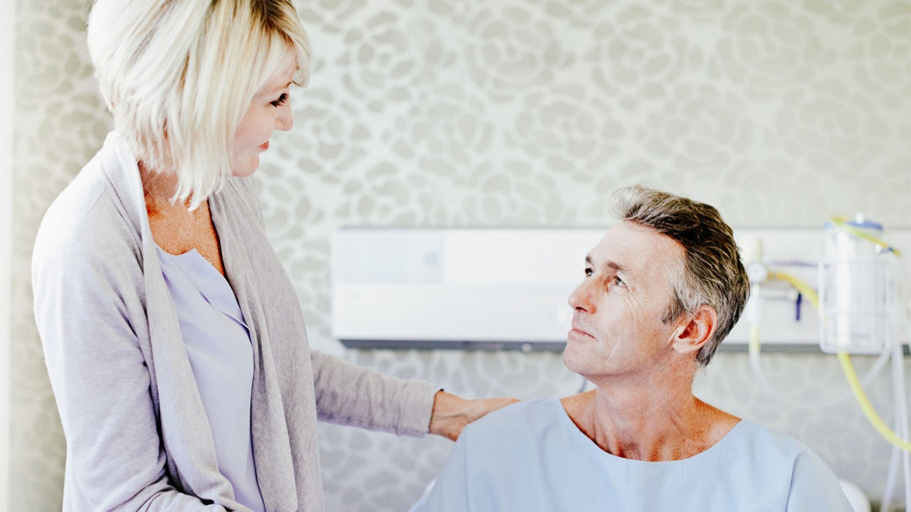 Woman talking to man wearing a hospital gown