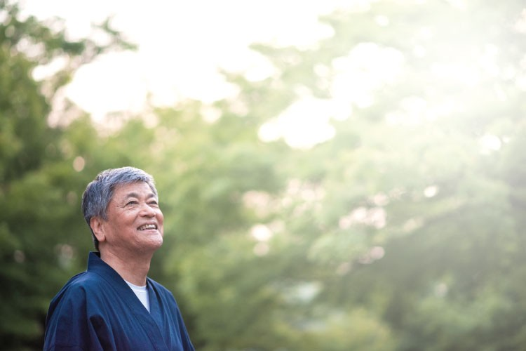 Chinese male smiling outdoors in a park while wearing kimono