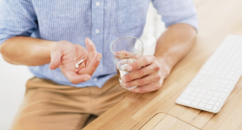 Man holding pills and glass of water