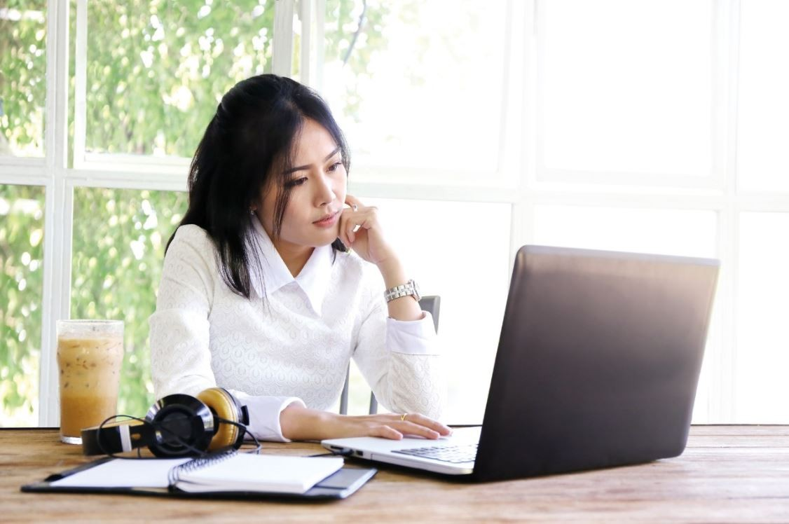 Young asian woman working on laptop with dairy drink
