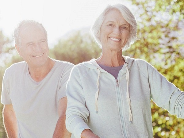 Senior couple walking bicycles in park healthy ageing medical nutrition