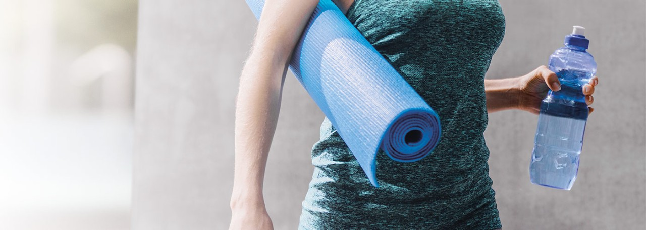 Western female walking with yoga mat and water bottle